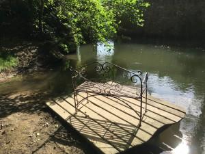 Banc en fer forgé au bord du ruisseau